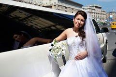 Mariée heureuse près de limousine de mariage Photographie stock libre de droits