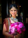 Mariée indienne de sourire avec le bouquet Photos libres de droits