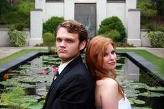 Mariée, marié s'asseyant par l'étang de lis Images stock