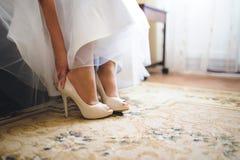 Mariée mettant sur des chaussures images stock