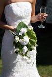 Mariée retenant un bouquet des fleurs et de la boisson Image stock