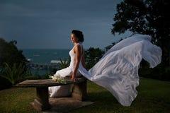 Mariée s'asseyant avec la robe soufflant dans le vent Image stock