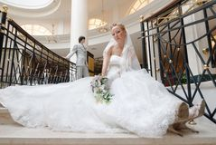 Mariée sur l'escalier. Sur le fond est le marié Photographie stock