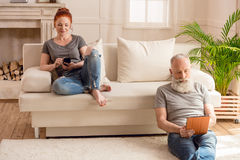 Mari à l'aide du comprimé numérique et se reposant sur le plancher tandis qu'épouse employant le smartphone et se reposer Photos stock