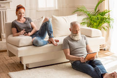 Mari à l'aide du comprimé numérique et se reposant sur le plancher tandis qu'épouse employant le smartphone et se reposer Image libre de droits