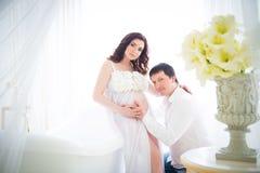 Mari étreignant le ventre d'une épouse enceinte avec la tendresse et soin Photographie stock libre de droits