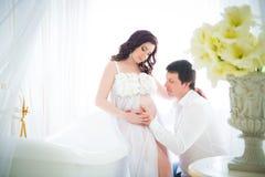 Mari étreignant le ventre d'une épouse enceinte avec la tendresse et soin Image stock