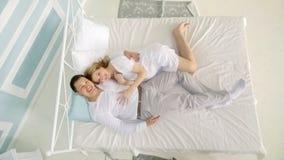 Mari affectueux avec une guitare et son épouse enceinte sur le lit dedans Photos libres de droits