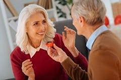 Mari affectueux traitant son épouse aux bonbons au chocolat Photographie stock libre de droits