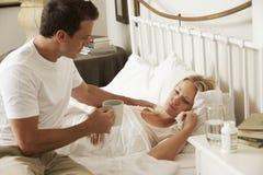 Mari apportant à épouse malade la boisson chaude dans le lit à la maison Images stock