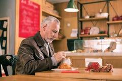 Mari barbu s'asseyant dans la boulangerie tout en attendant son épouse photo libre de droits