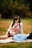 Mari beau se trouvant sur la jambe de sa jeune belle femme enceinte en parc Image stock