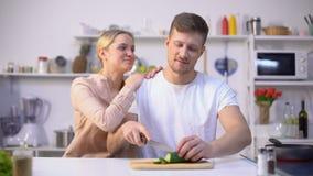 Mari découpant le légume en tranches, épouse aimante l'embrassant, moment romantique dans la cuisine clips vidéos