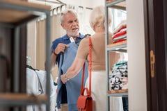 Mari d'une chevelure gris étant dans le doute tout en choisissant un pull avec son épouse photos stock