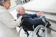 Mari de aide d'épouse sur le fauteuil roulant Image libre de droits