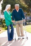 Mari de aide de femme aînée avec la trame de marche Photos libres de droits