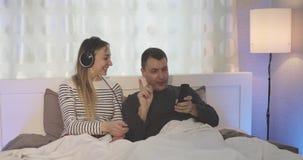 Mari et épouse dans des écouteurs regardant la TV dans la chambre à coucher banque de vidéos