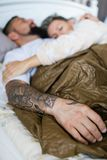 Mari et épouse dormant ensemble dans un lit - la main de l'homme tatoué images stock