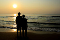 Mari et épouse embrassant en mer, silhouette Images stock
