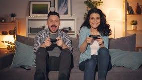 Mari et épouse jouant le jeu vidéo tenant des manettes se reposant sur le sofa à la maison clips vidéos