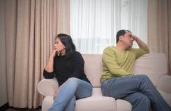 Mari et épouse s'asseyant de différents côtés de sofa escroquerie de querelle photos stock