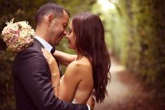 Marié et jeune mariée embrassant dans le jardin Image libre de droits