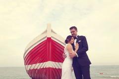 Marié et jeune mariée près d'un bateau rouge Image stock