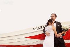 Marié et jeune mariée près d'un bateau rouge Images stock