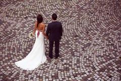 Marié et jeune mariée sur le trottoir Photos stock
