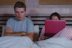 Mari fâché et frustrant déprimé dans le lit ignoré par son amie sociale d'épouse de bourreau de travail ou d'intoxiqué de médias  image libre de droits