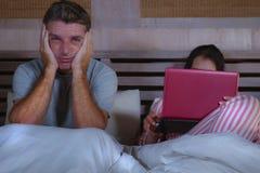Mari fâché et frustrant déprimé dans le lit ignoré par son amie sociale d'épouse de bourreau de travail ou d'intoxiqué de médias  images libres de droits