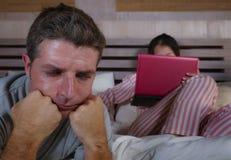Mari fâché et frustrant déprimé dans le lit ignoré par son amie sociale d'épouse de bourreau de travail ou d'intoxiqué de médias  image stock