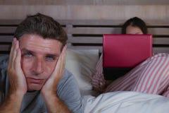 Mari fâché et frustrant déprimé dans le lit ignoré par son amie sociale d'épouse de bourreau de travail ou d'intoxiqué de médias  photos stock