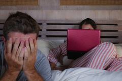 Mari fâché et frustrant déprimé dans le lit ignoré par son amie sociale d'épouse de bourreau de travail ou d'intoxiqué de médias  photo libre de droits