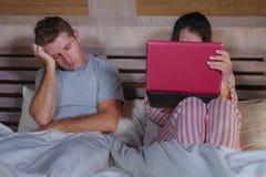 Mari fâché et frustrant déprimé dans le lit ignoré par son amie sociale d'épouse de bourreau de travail ou d'intoxiqué de médias  photo stock
