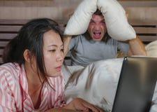 Mari frustrant déprimé dans le lit ignoré par son amie sociale asiatique d'épouse de bourreau de travail ou d'intoxiqué de médias photographie stock libre de droits