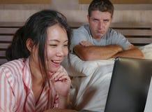 Mari frustrant déprimé dans le lit ignoré par son amie sociale asiatique d'épouse de bourreau de travail ou d'intoxiqué de médias images stock