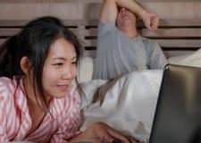 Mari frustrant déprimé dans le lit ignoré par son amie sociale asiatique d'épouse de bourreau de travail ou d'intoxiqué de médias photo libre de droits