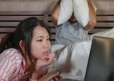 Mari frustrant déprimé dans le lit ignoré par son amie sociale asiatique d'épouse de bourreau de travail ou d'intoxiqué de médias images libres de droits