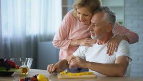 Mari handicapé faisant cuire le dîner dans la cuisine, épouse de soin l'étreignant, appui banque de vidéos