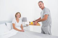 Mari heureux apportant le petit déjeuner dans le lit à l'épouse Photos libres de droits