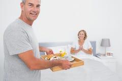 Mari heureux apportant le petit déjeuner dans le lit à l'épouse avec plaisir Image stock