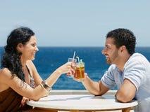 Mari heureux et épouse grillant avec des cocktails Photo stock
