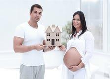 Mari montrant à son épouse enceinte une disposition de leur future maison photo stock