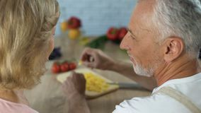 Mari plus âgé traitant l'épouse avec des légumes, relations de famille, dîner à la maison banque de vidéos