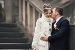 Marié romantique embrassant la jeune mariée heureuse dans le manteau sur les escaliers en pierre Images stock