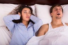 Mari snorring de observation de femme éveillée la nuit Image libre de droits