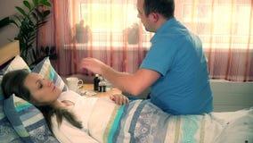 Mari soigneux s'asseyant contre l'épouse malade dans le lit d'hôpital banque de vidéos