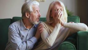Mari supérieur aimable affectueux consolant l'épouse âgée moyenne pleurante triste banque de vidéos