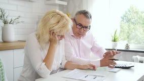 Mari supérieur et épouse mûre calculant les finances à la maison dans la cuisine clips vidéos